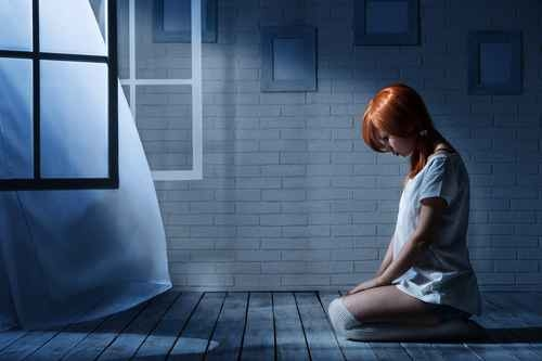 Lonely girl sits in an empty dark room opposite the window
