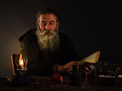 Un moine de l'ordre des templiers contemple un livre